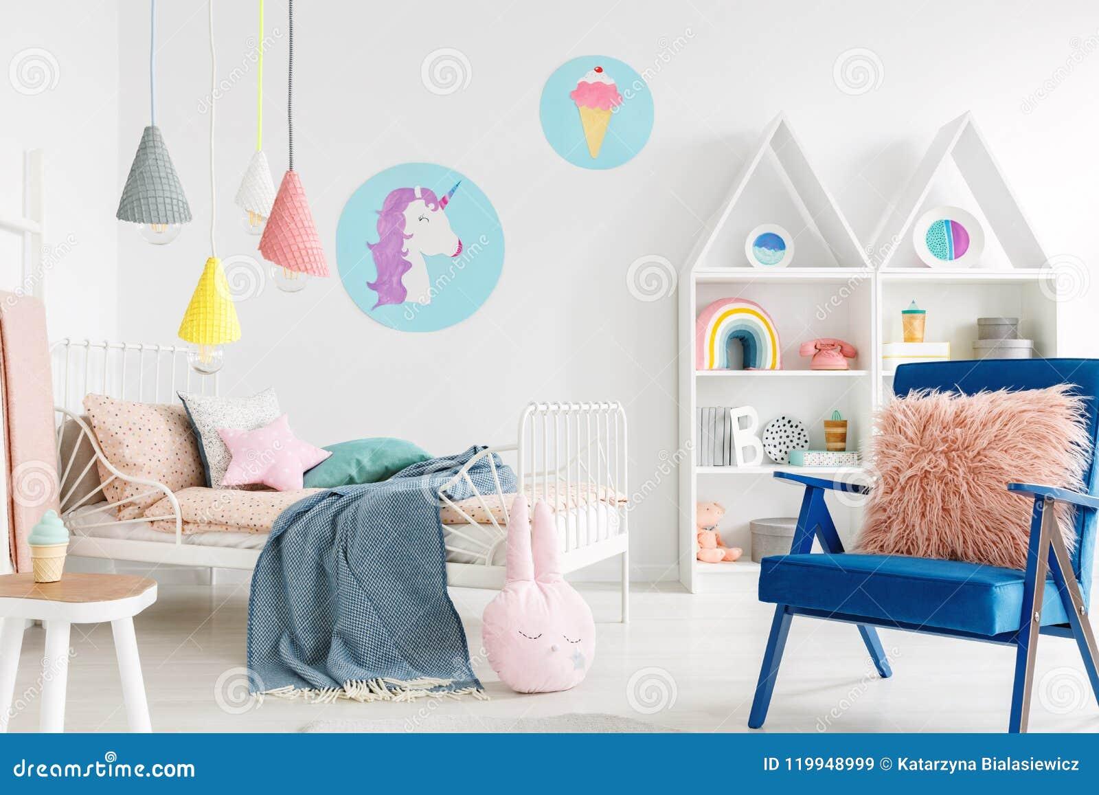 Bont roze hoofdkussen op een trillende blauwe leunstoel in een zoet jong geitje bedr
