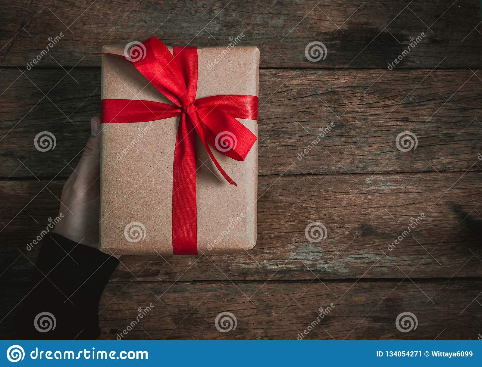 ffb986078c90 Bonus human man hand give a present Brown Gift box bow tie Red ribbon On old  wood floor top view merry christmas and happy new year concept