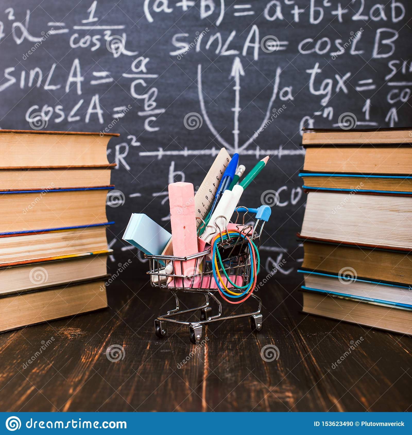 Boodschappenwagentje met schoollevering, op de lijst met boeken tegen de achtergrond van een bord Concept terug naar school