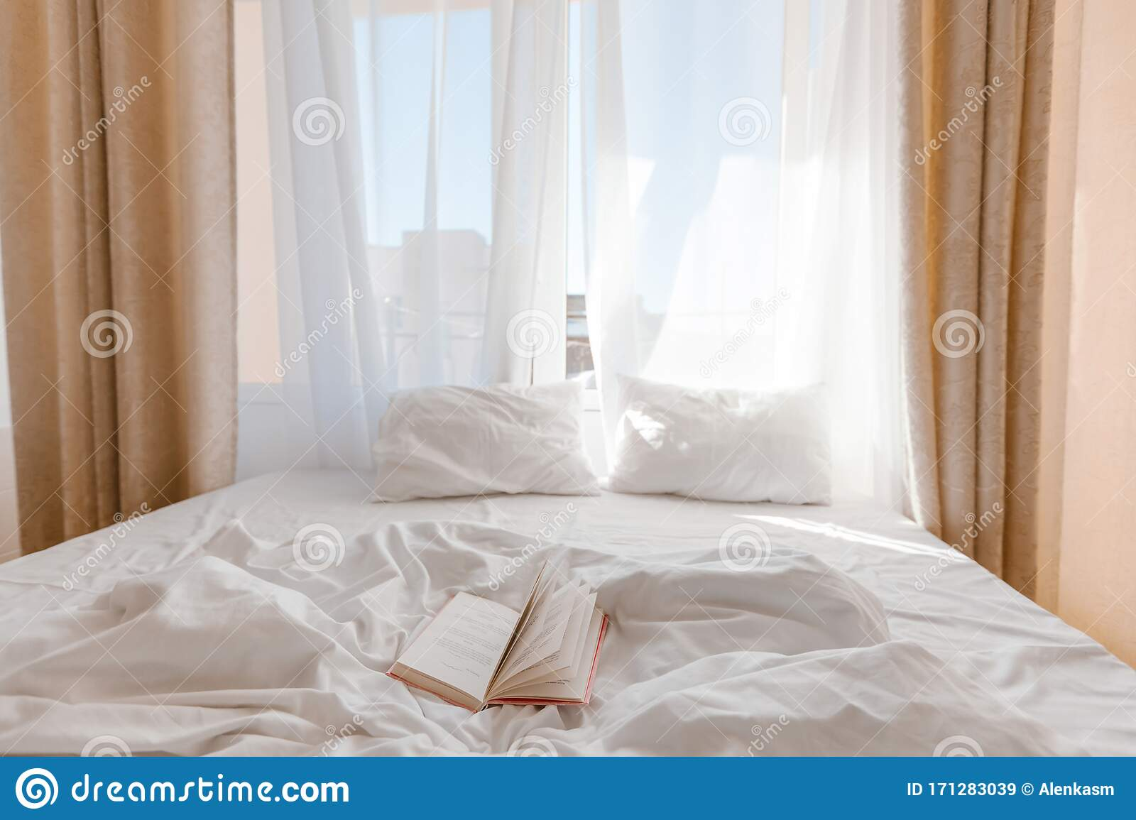 Book On Bed With White Linen In Front Of Window With Morning Light Through Curtains Stock Image Image Of Inspiration Resort 171283039