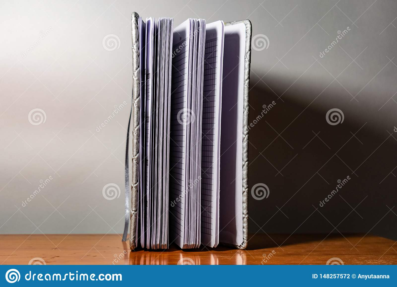 A book, a notebook with a checkered pattern on a wooden table in different poses. The cover is grey and soft with texture. Square