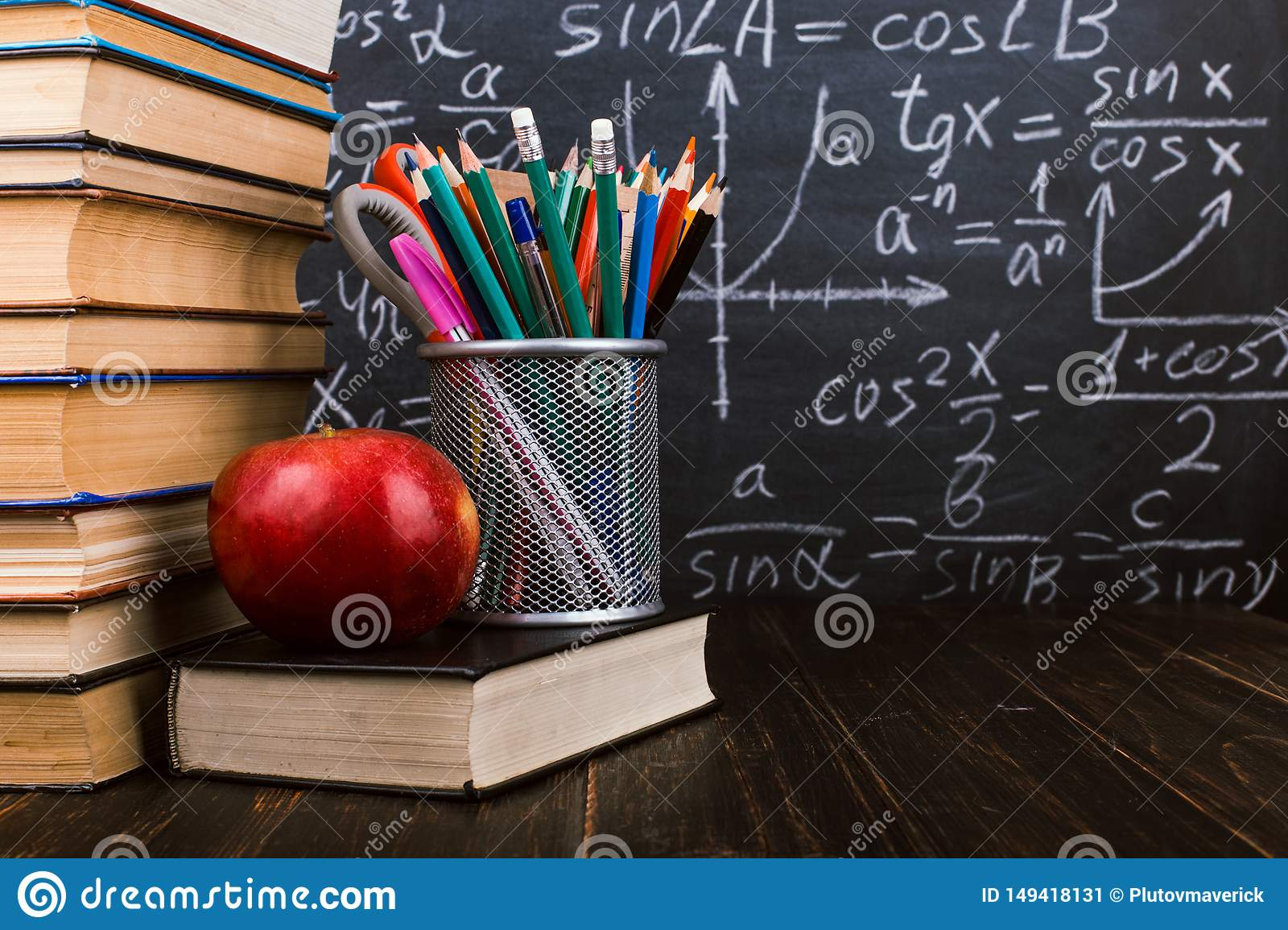 Books, an apple, stand for pens on wooden table, against the background of chalk board with formulas. Teacher`s day concept and