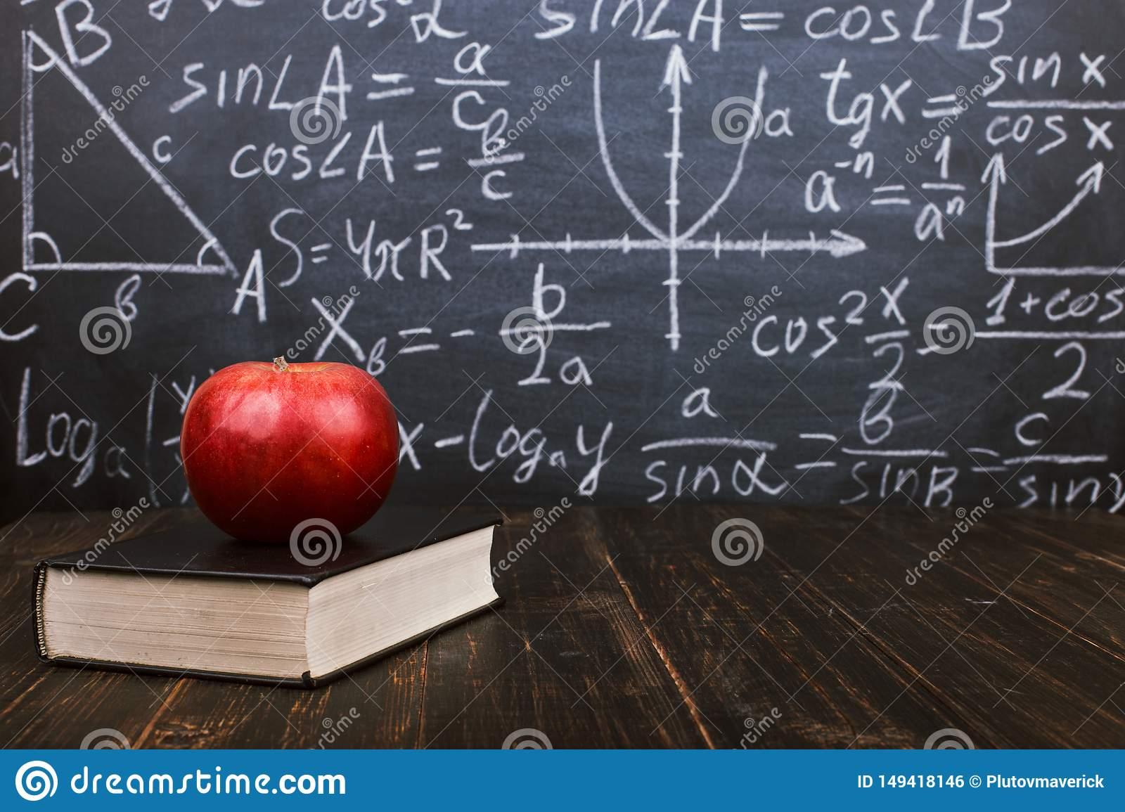 Books and an apple on a wooden table, against the background of a chalkboard with formulas. Teacher's day concept and back to