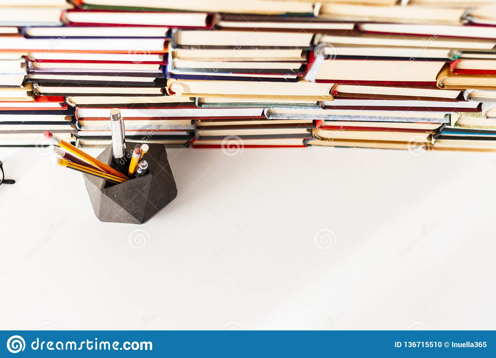 Books background, glasses, pens and pencils on white wooden table