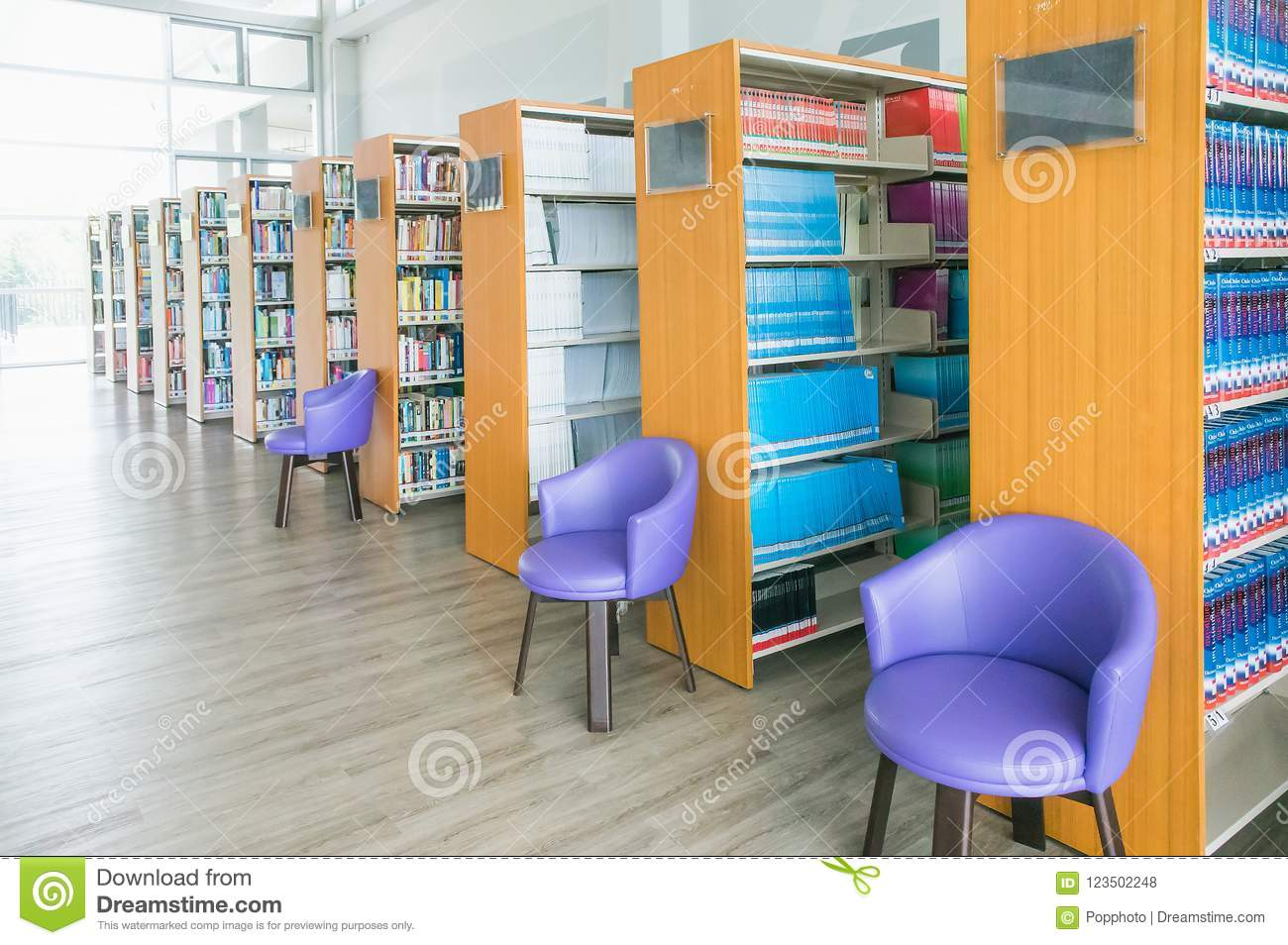 The Books On Bookshelf And Purple Chairs In Interior Library Of University