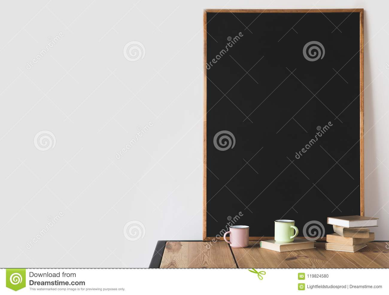 books and cups with big blackboard on wooden table on white