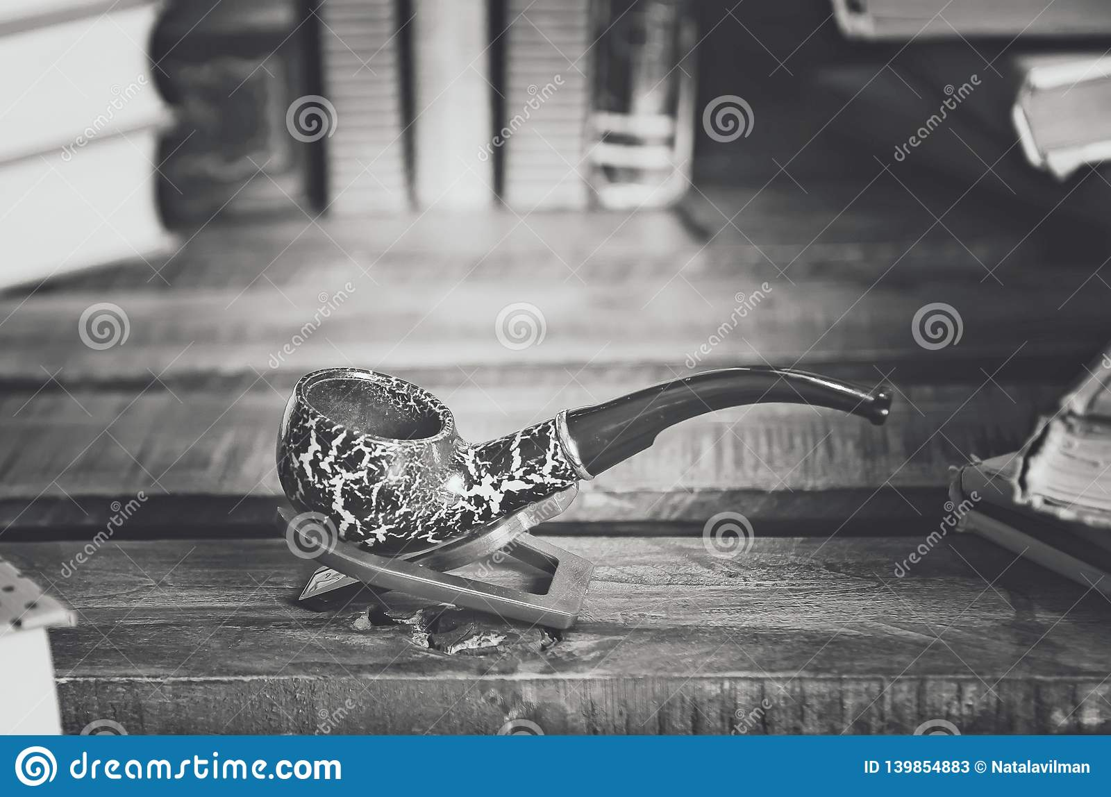 Books and a smoking pipe on a wooden table. Beautiful stylish composition. Вlack and white photography