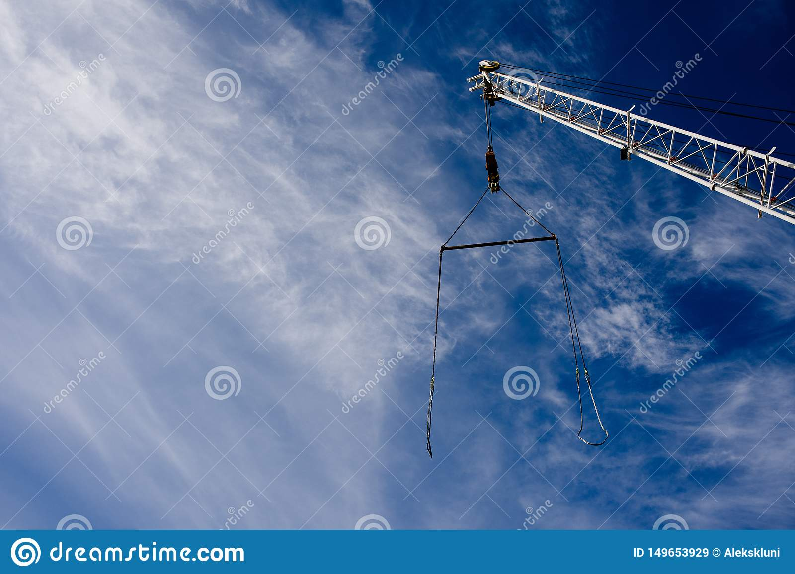 Boom crane with a cable against the blue sky. Background. Copy space