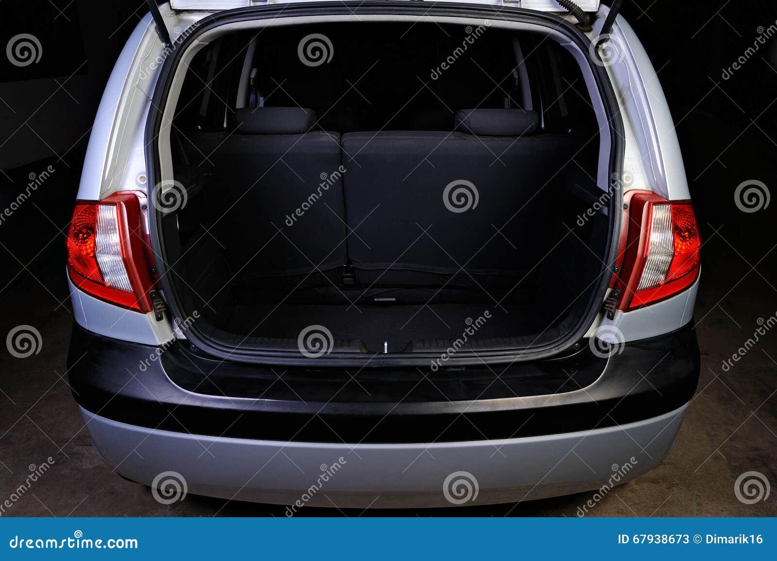 Boomstam van vijfdeursauto op zwarte