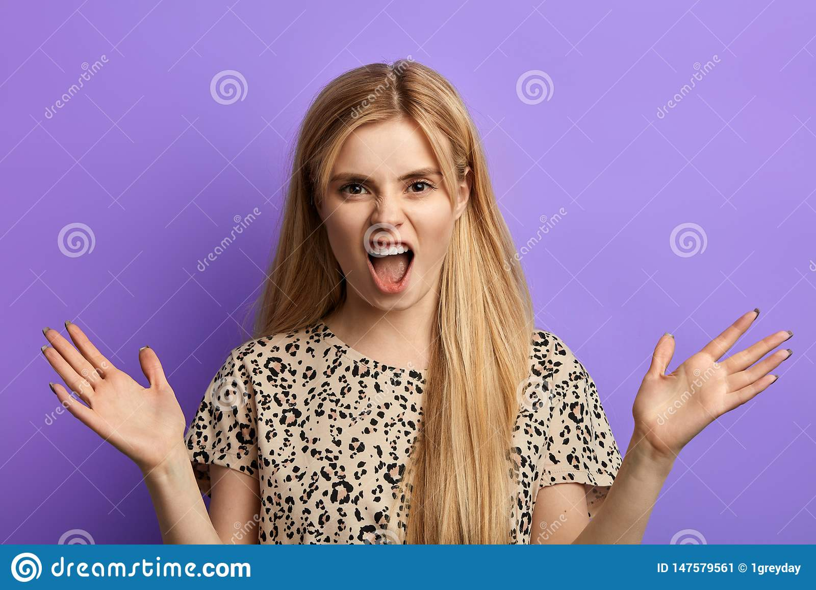 Boos die blondemeisje met handen het schreeuwen bij camera worden opgeheven