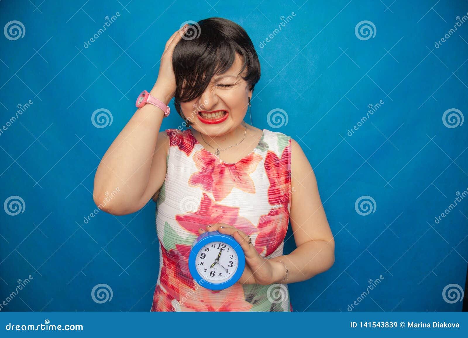 Boos gillend ongelukkig meisje die een ronde wekker op blauwe studioachtergrond houden