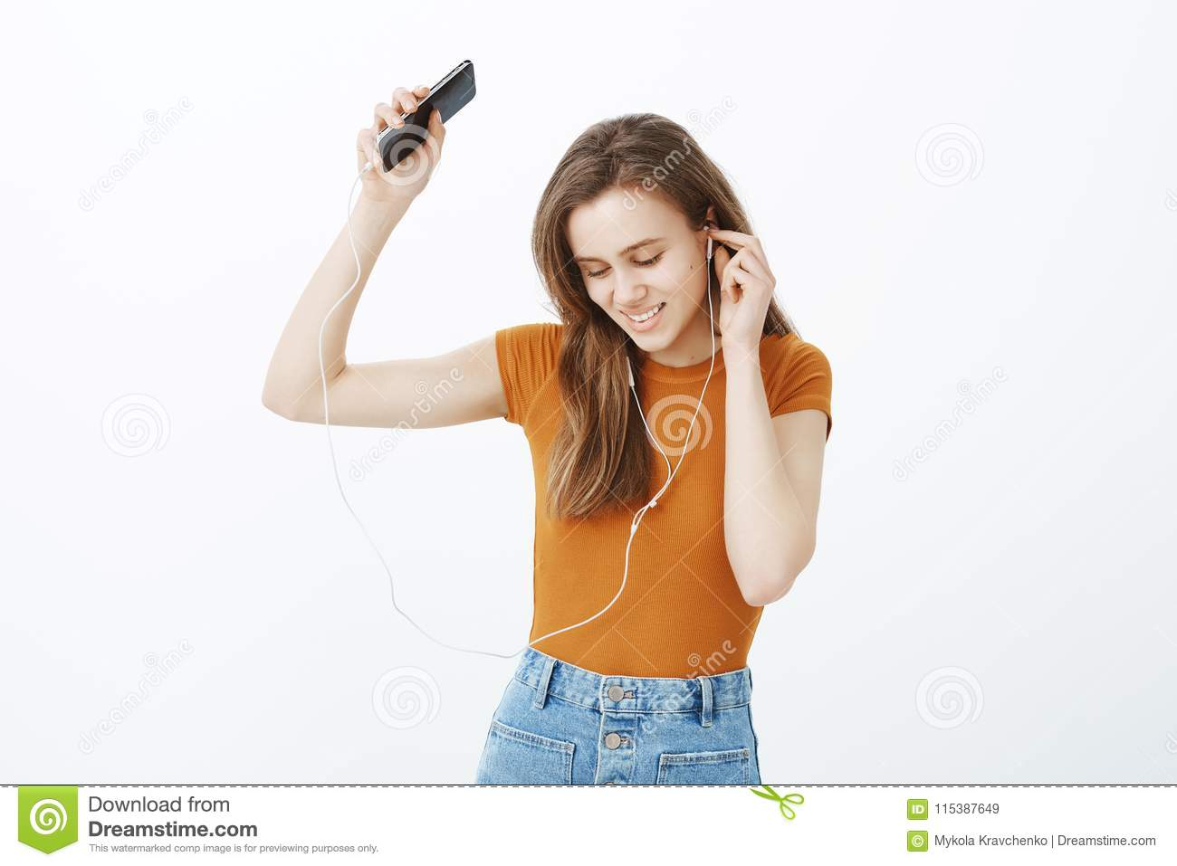 Boosting happy mood with favorite songs. Relaxed charming european female student in colorful clothes, raising hand with