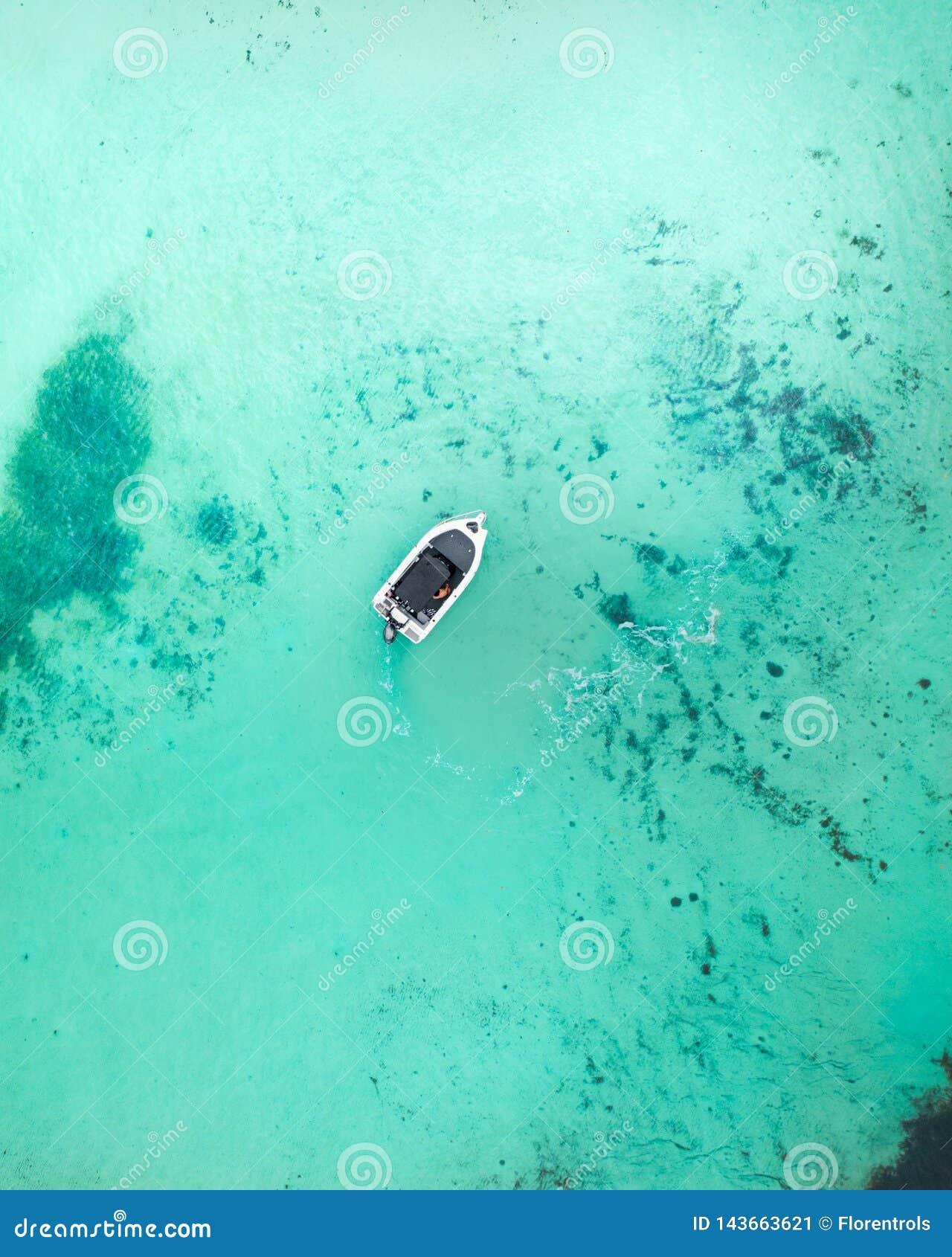 Boot die door het blauwe water bij zonsopgang kruisen