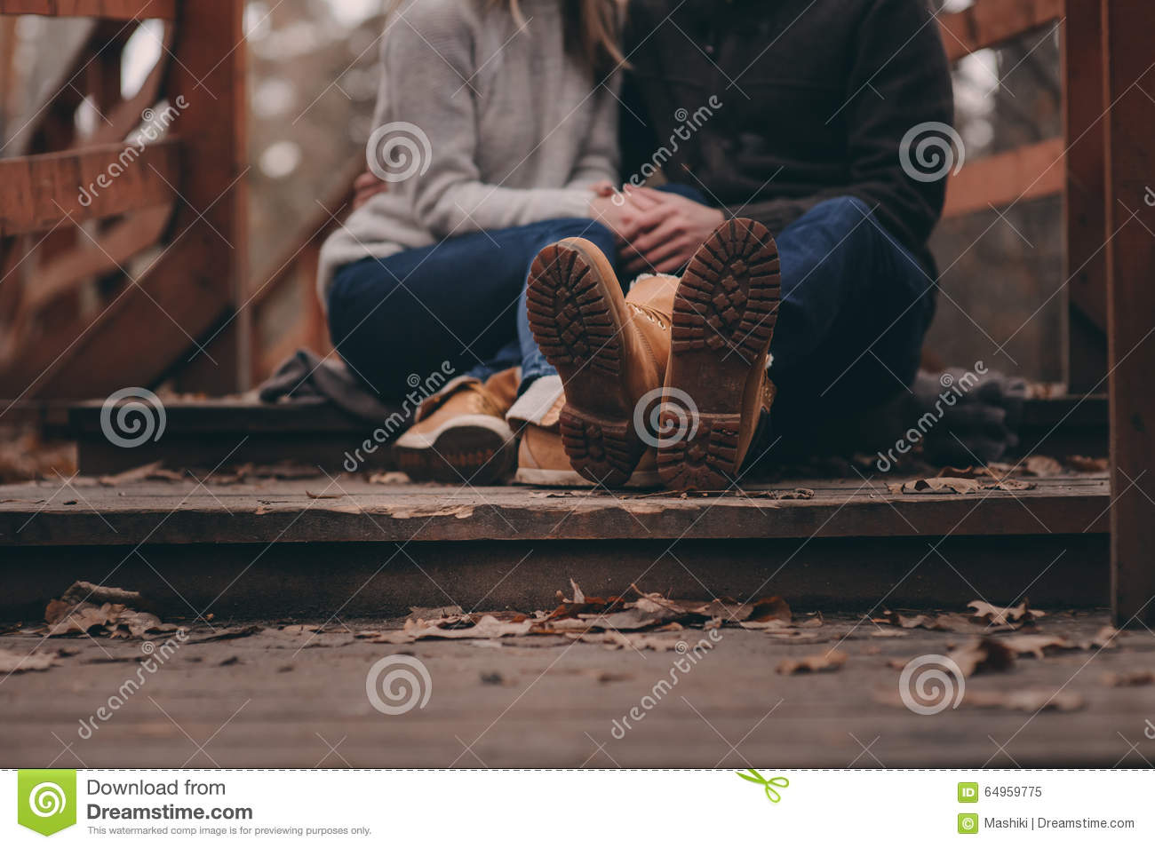 Boots of young couple walking outdoor on wooden bridge in autumn
