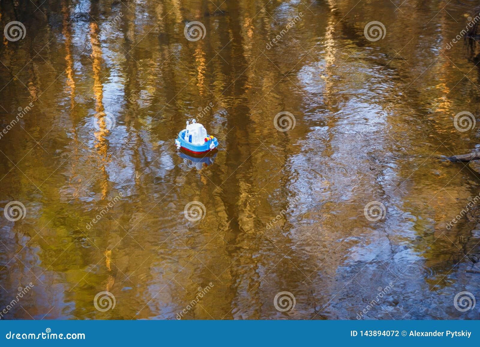 Bootsblau der Kinder geht auf das goldene Wasser