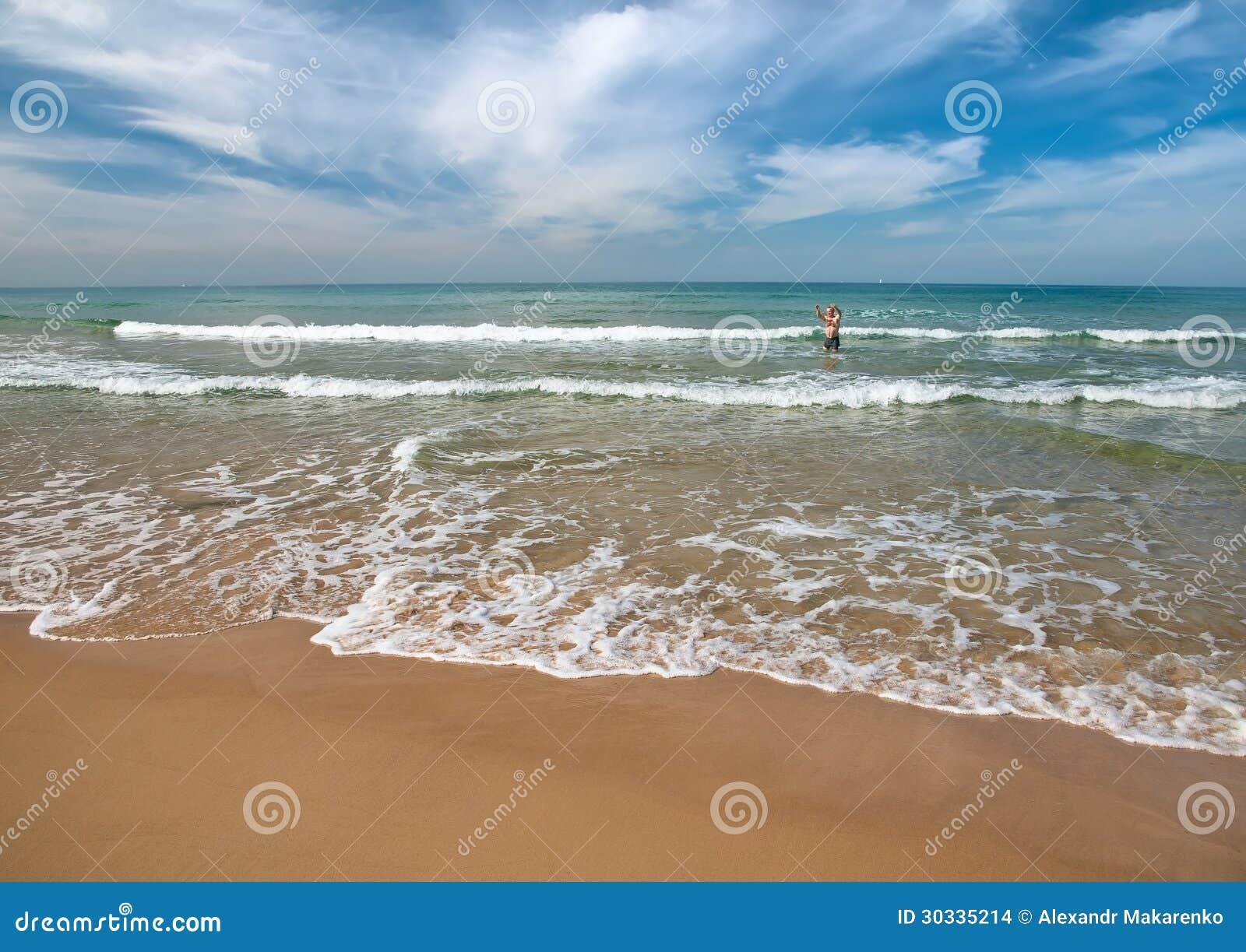 Bord de la mer avec des baigneurs à l arrière-plan.