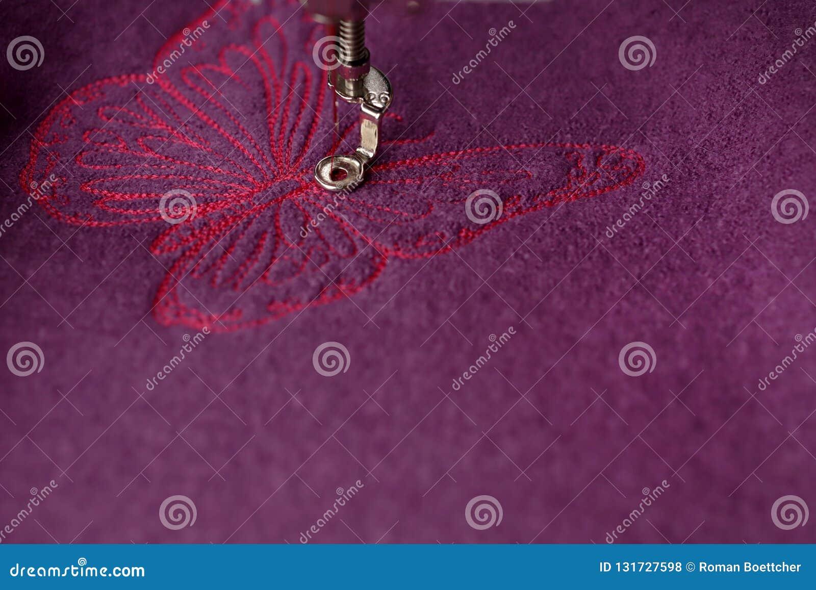 Bordado detallado de la mariposa rosada en las lanas hervidas púrpuras con una máquina del bordado