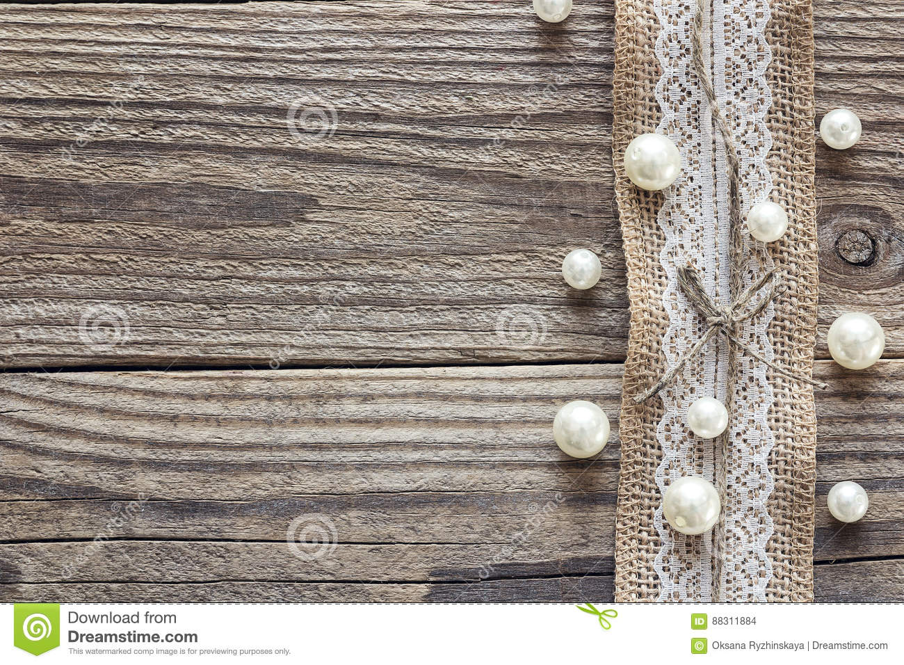 Border of burlap with white lace and beads on old wooden table.
