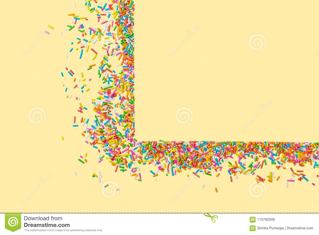 Border frame of colorful sprinkles on a yellow background with c