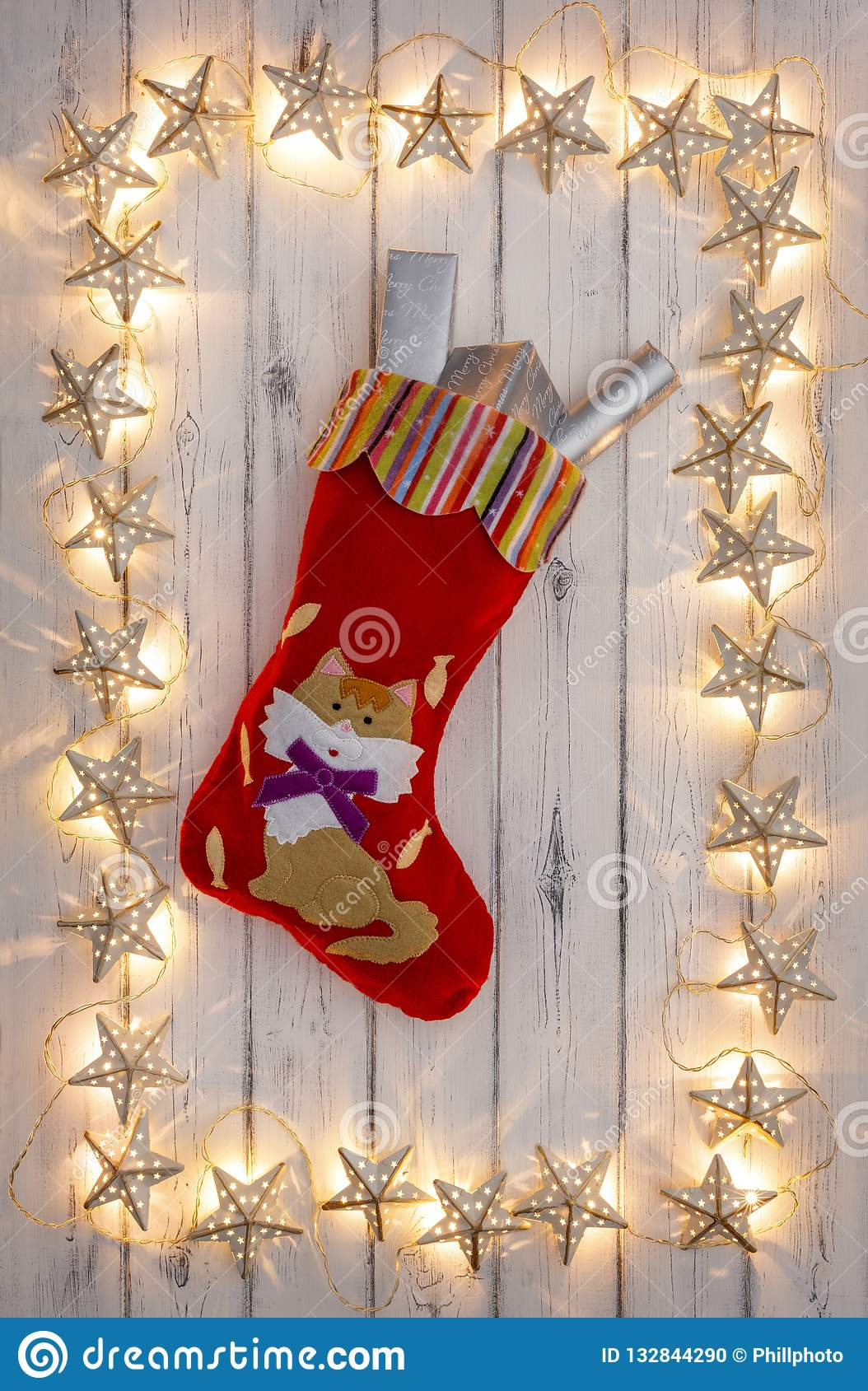 A border of golden star christmas lights, with a kittens christmas stocking and presents, on a destressed woodern background