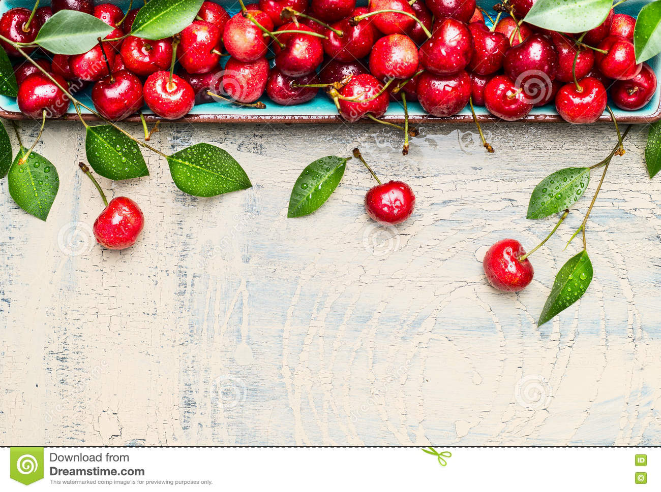 Border of sweet cherries with green leaves on light wooden background, top view, place for text