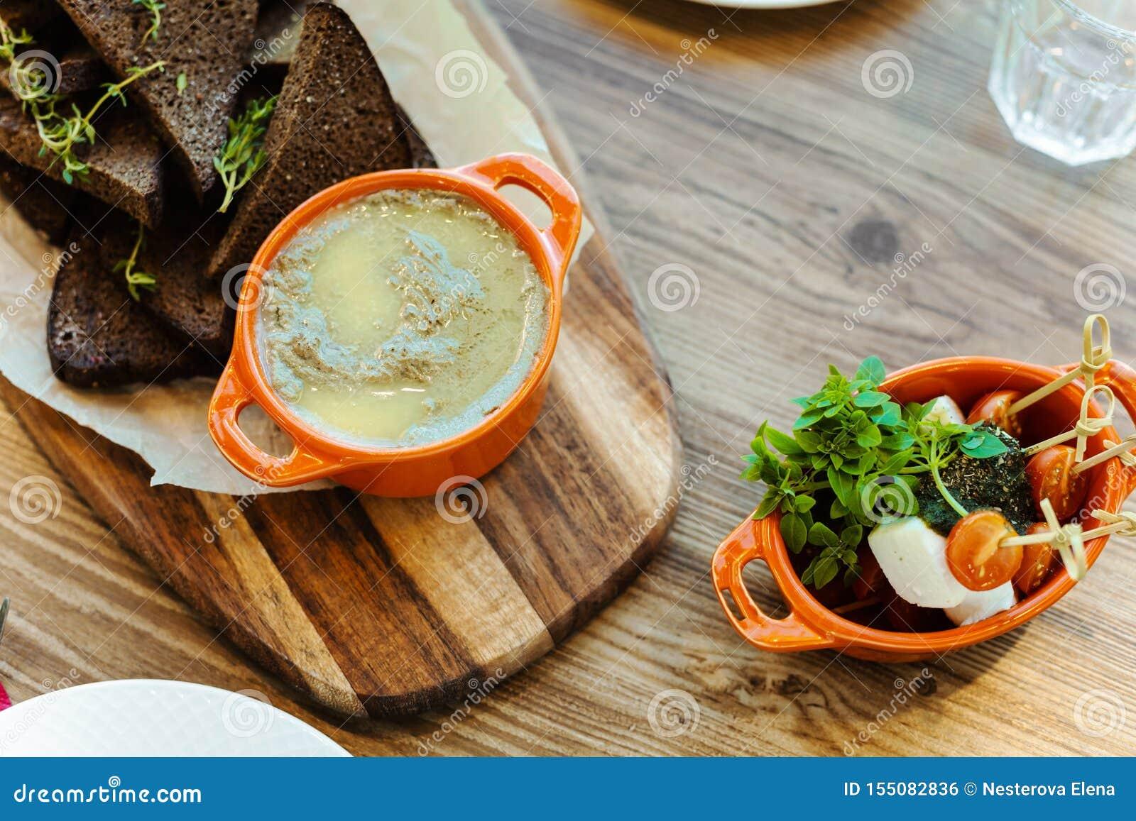 Bordo con i cracker della segale con i rosmarini, pasticcio di fegato casalingo e un piatto con formaggio, pomodori ciliegia fres