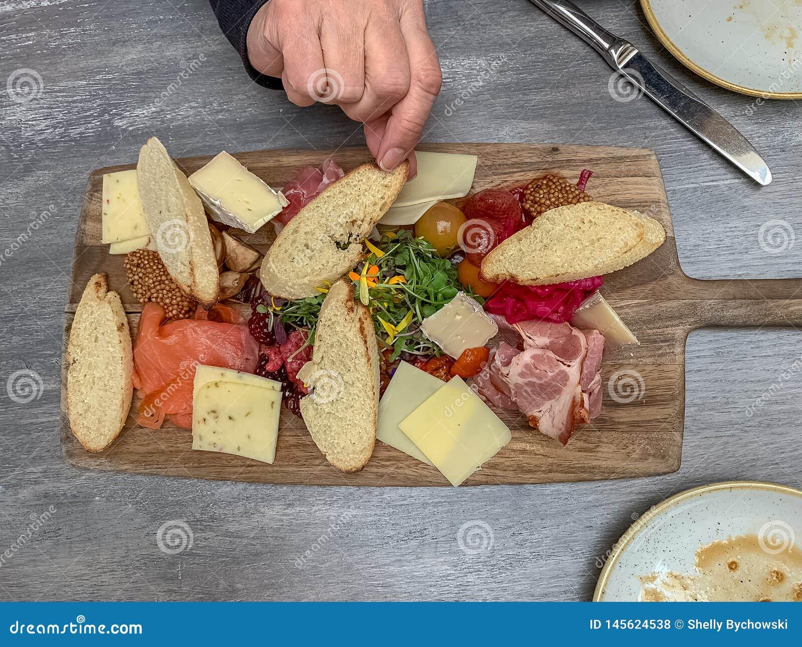 Bordo del Charcuterie con la mano della donna che raggiunge per la fetta di pane