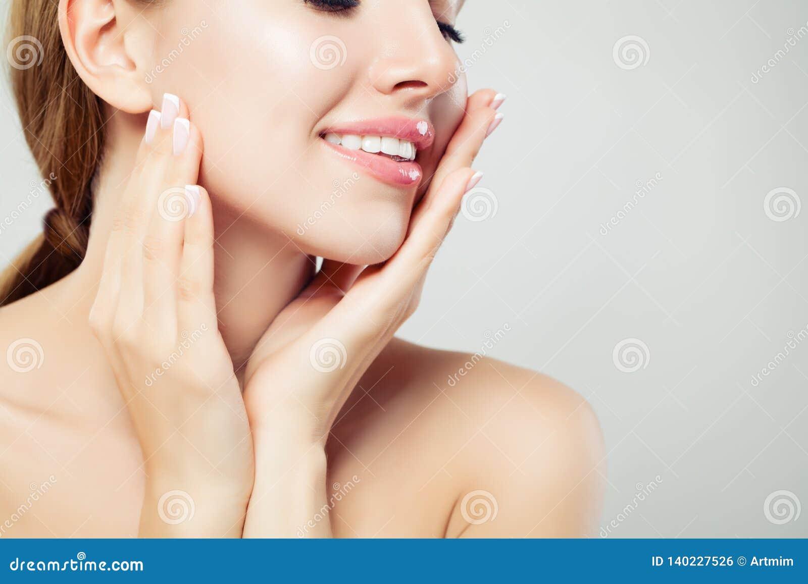 Bordos saudáveis da mulher com composição cor-de-rosa lustrosa e mãos manicured com os pregos do tratamento de mãos francês, clos