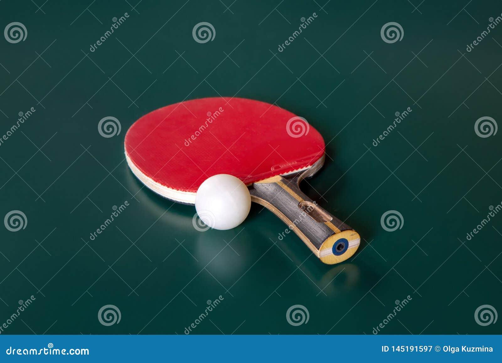 Bordtennisracket och en boll p? en gr?n tabell
