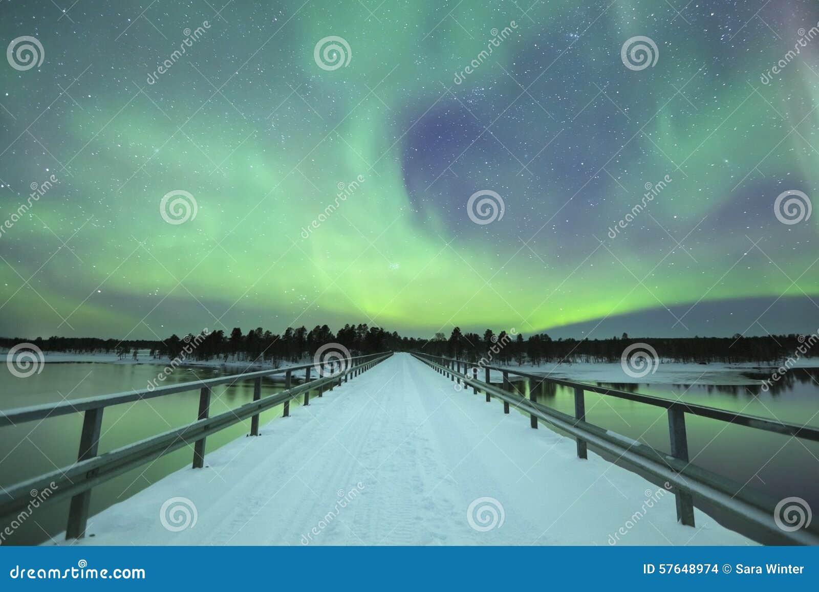 Borealis αυγής πέρα από μια γέφυρα το χειμώνα, φινλανδικό Lapland