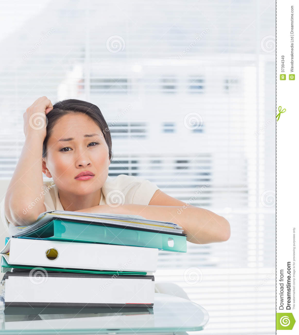 On Desk Bored businesswoman with stack of folders at desk royalty