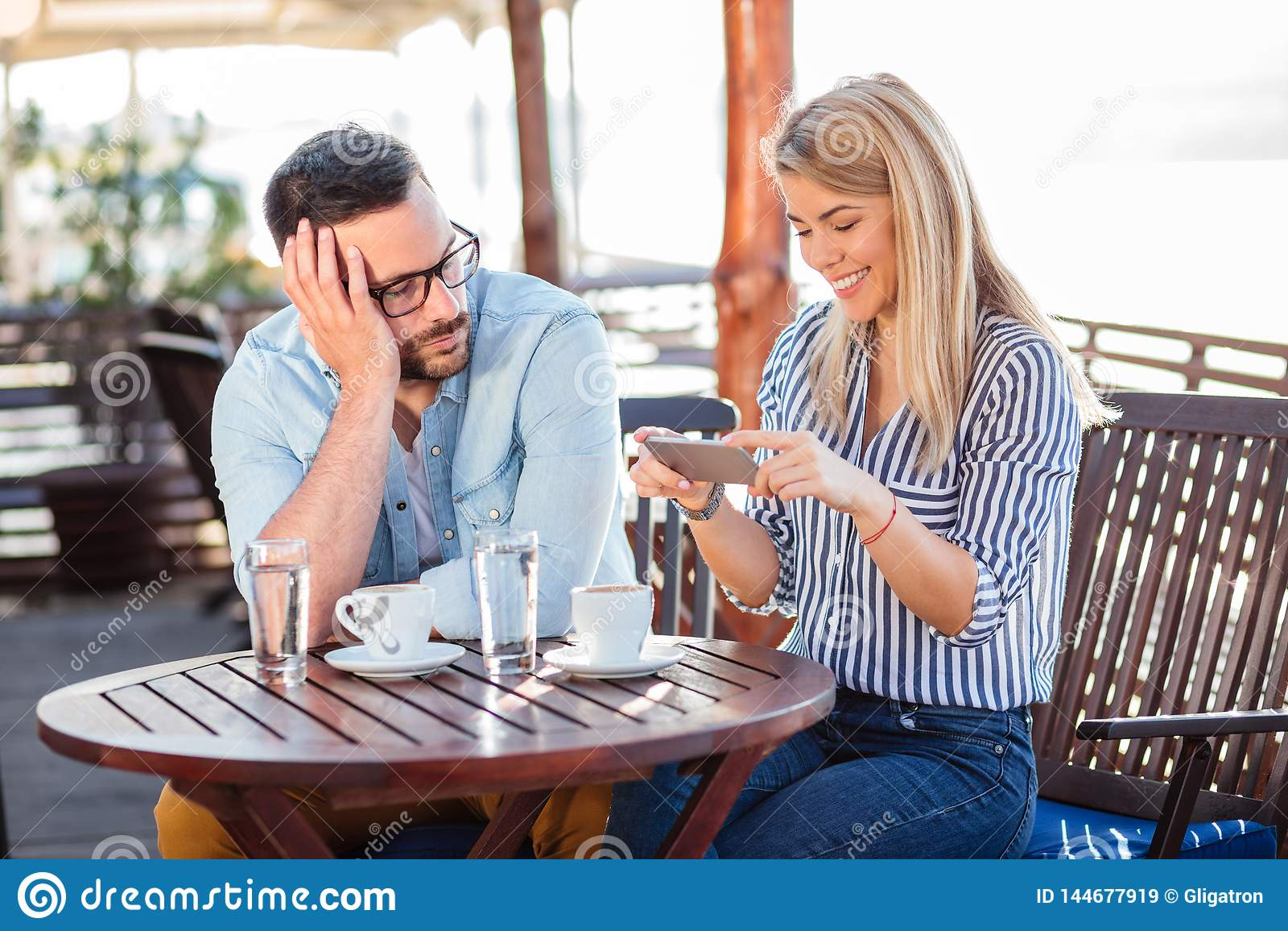 Bored jonge mens die op zijn meisje wachten ophouden gebruikend de telefoon