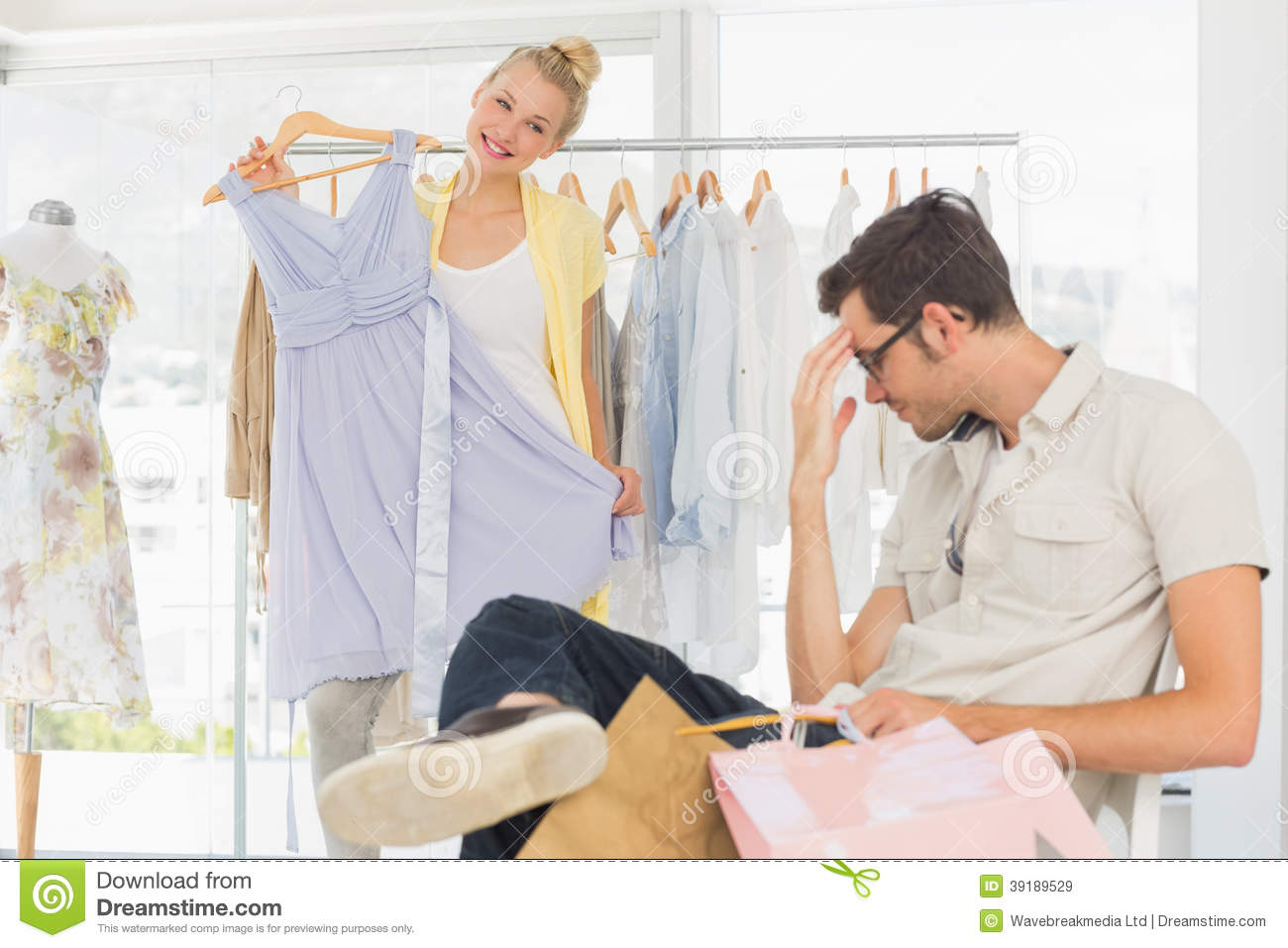 Bored Man With Shopping Bags While Woman At Clothes Rack ...