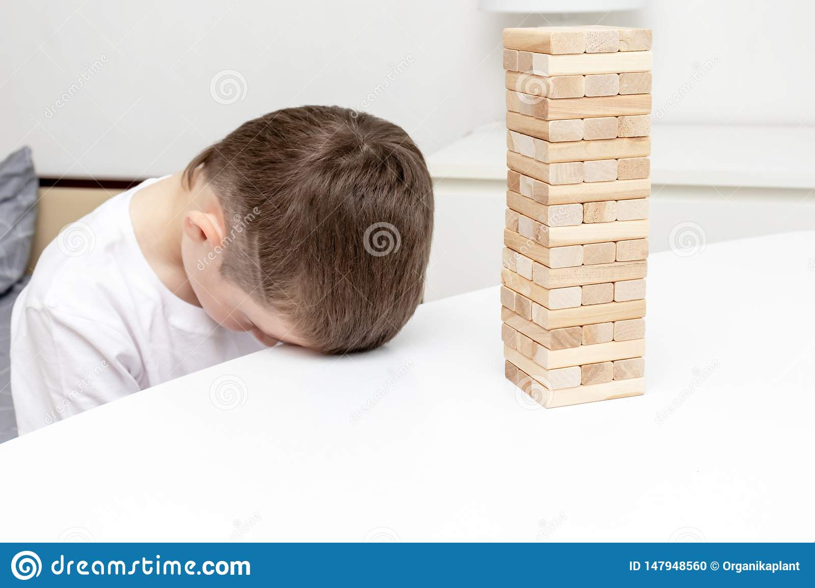 A bored preteen caucasian boy trying to play wooden block tower board game to entertain himself