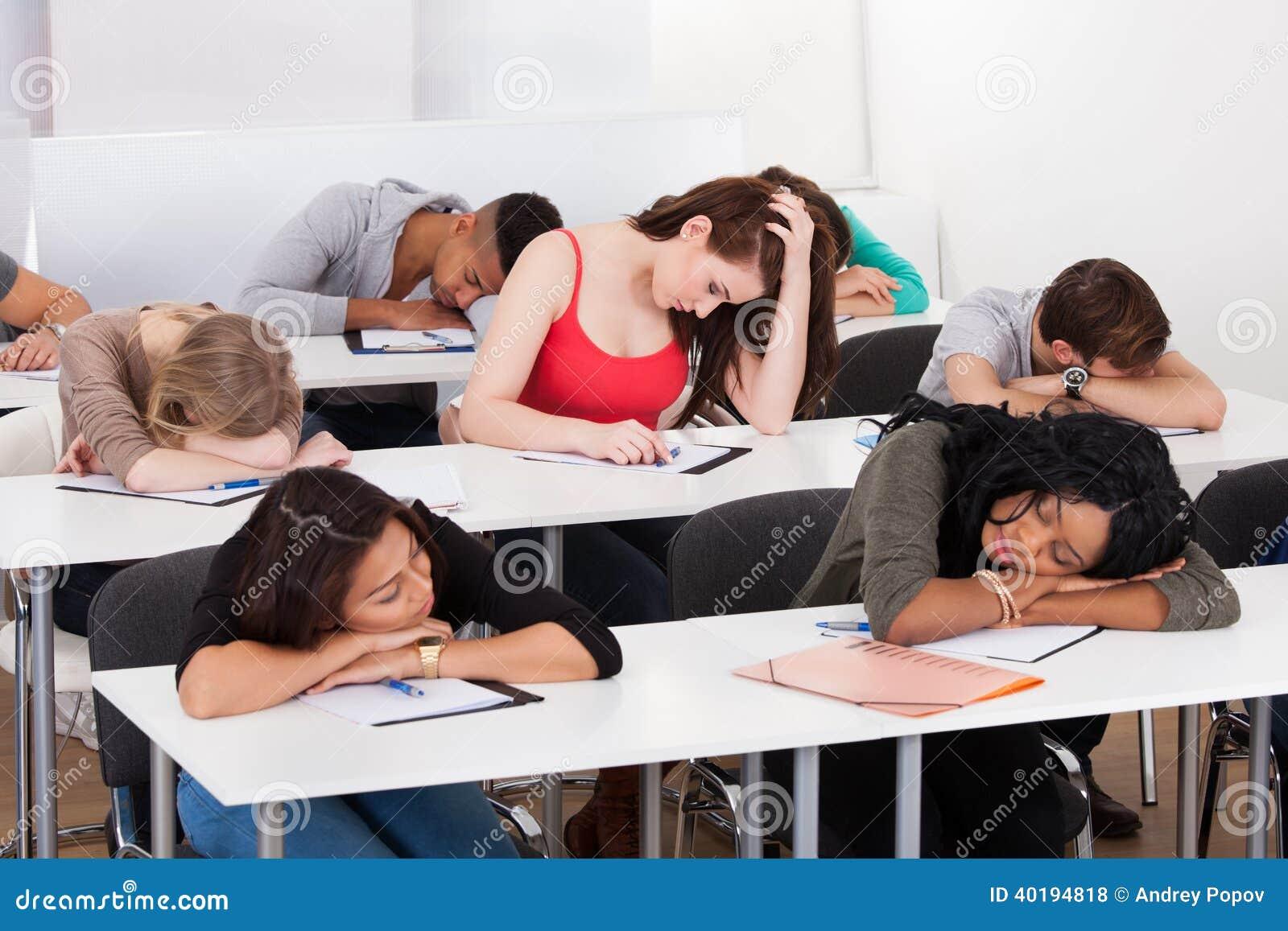 Bored student met klasgenoten die bij bureau slapen
