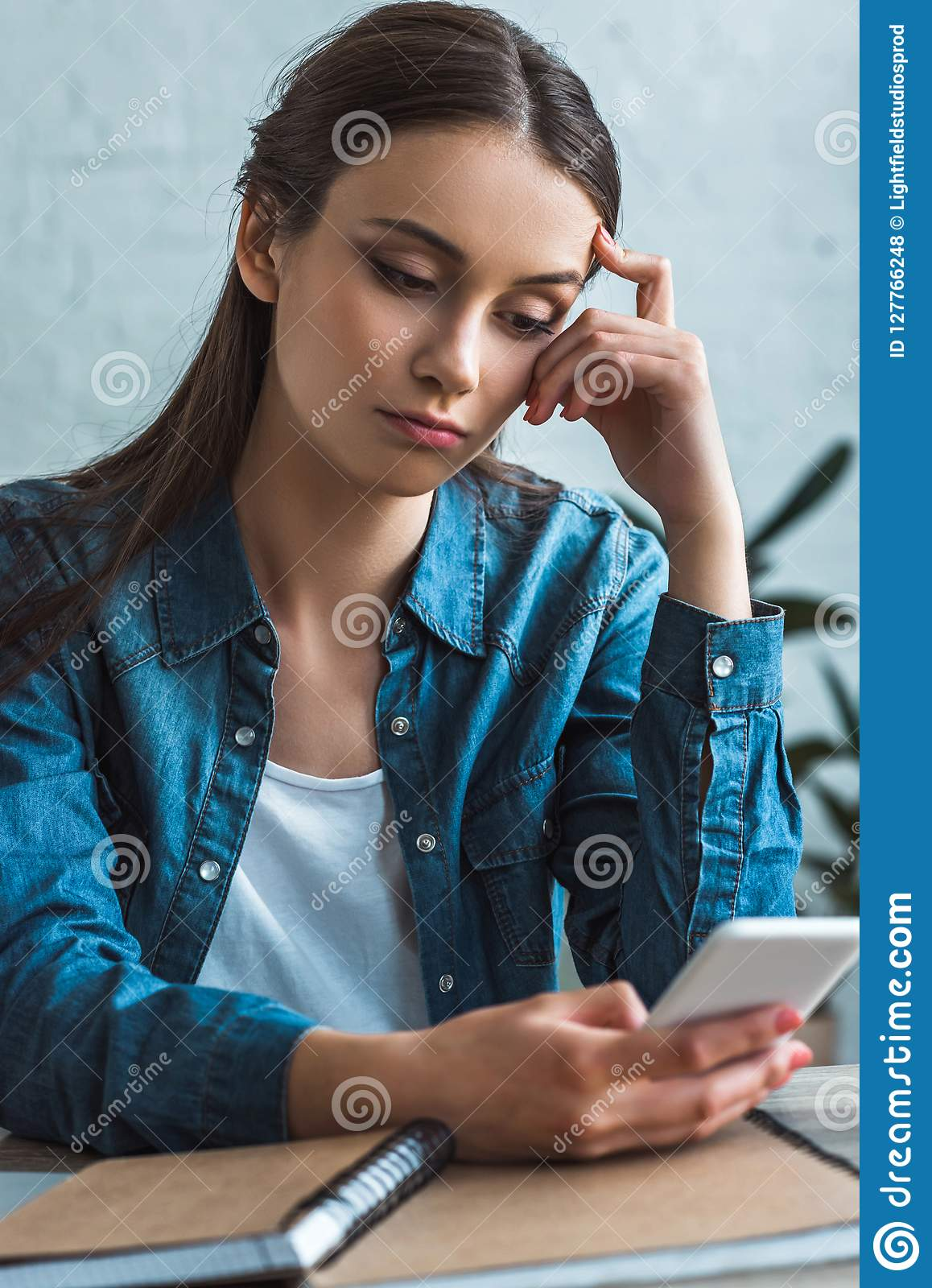 bored teenage girl using smartphone while sitting at table with notebooks