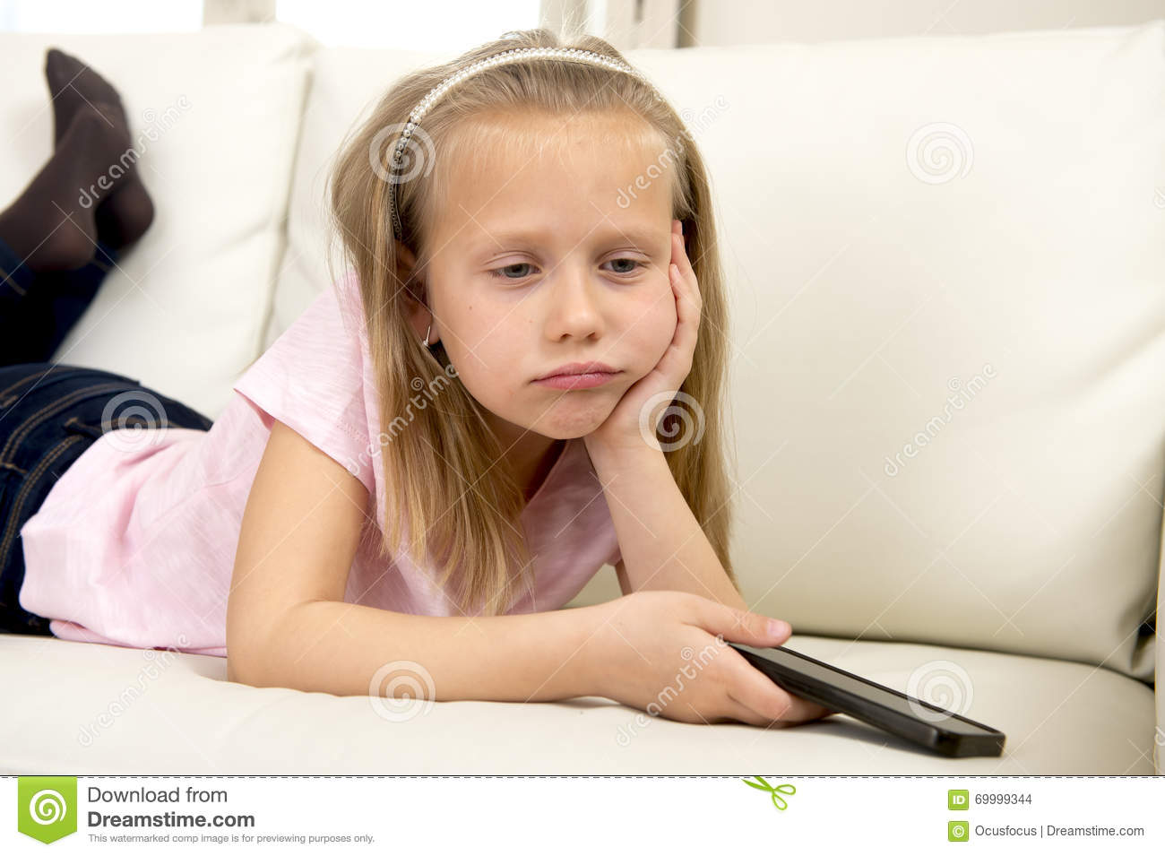 eb6f5fdff Bored and tired blond little girl on home sofa using internet app on mobile  phone