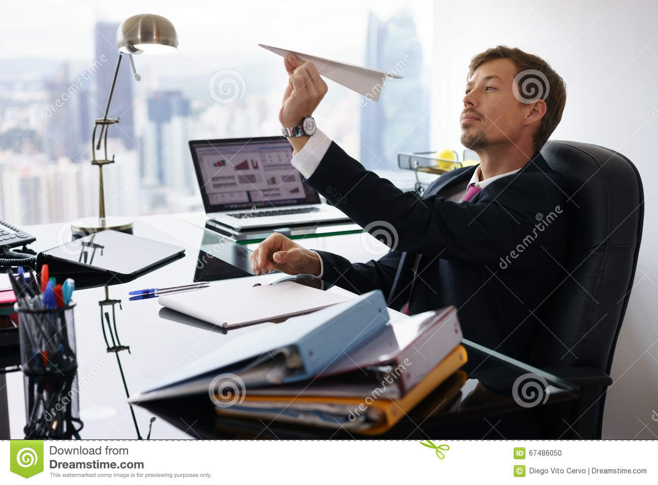 Bored Business Man Throwing Paper Airplane In Office Stock