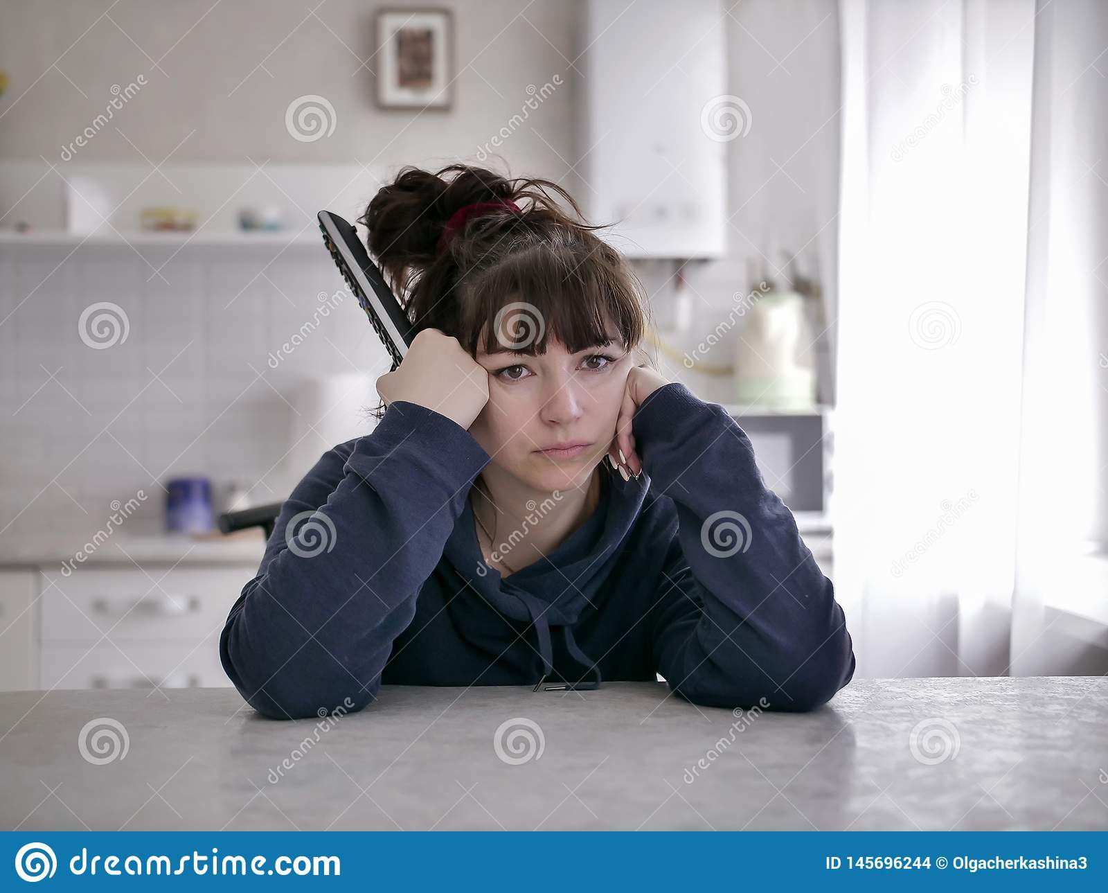 Bored woman sitting with remote control on a blurred background of the kitchen