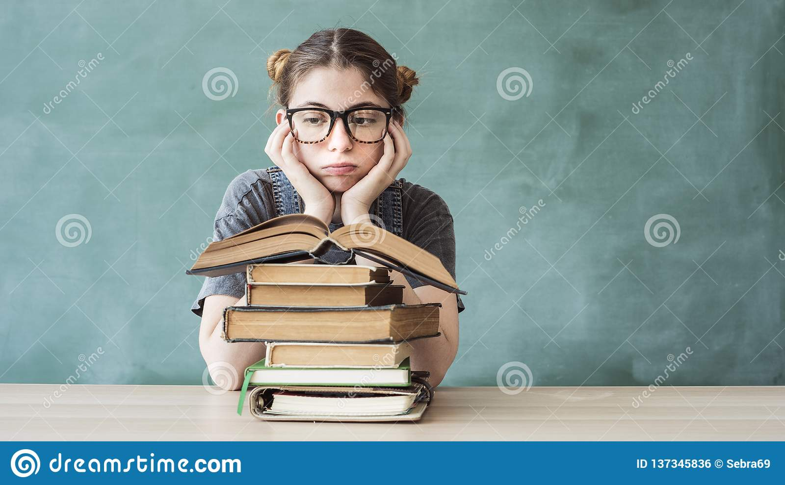 Bored young student girl with books