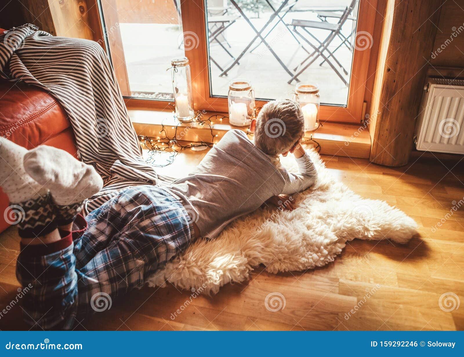 Boring Boy Ligt Op De Vloer En Kijk Uit Het Raam In Luie En Warme Woonkamer Stock Foto Afbeelding Bestaande Uit Eenzaamheid Kids 159292246