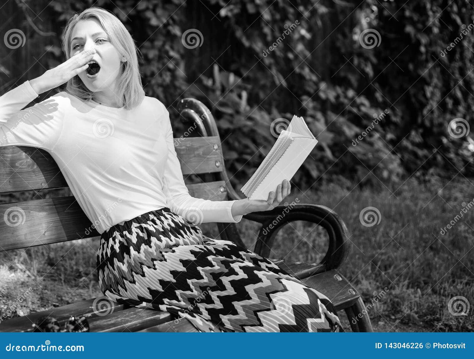 Boring literatuur Neemt het vrouwen geeuwende blonde onderbreking het ontspannen in het boek van de tuinlezing Het meisje zit ban