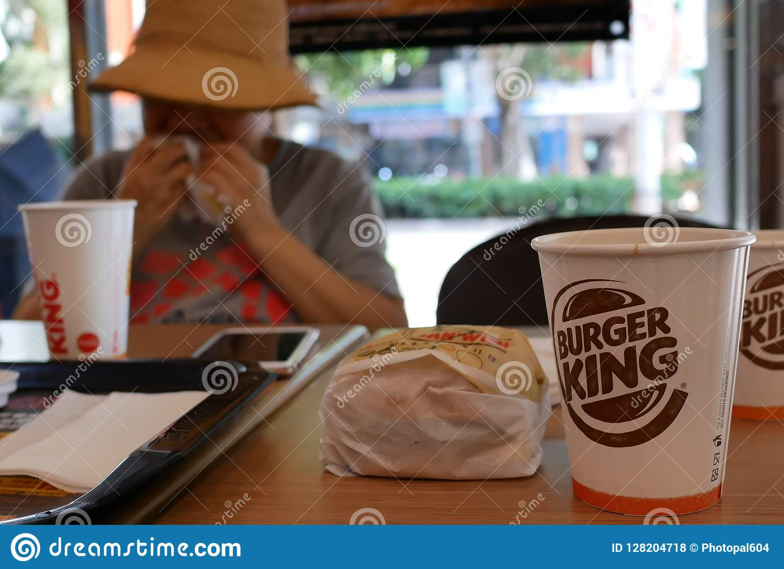 Borre o movimento da mulher que come o hamburguer e que bebe o café quente no restaurante do fast food de Burger King
