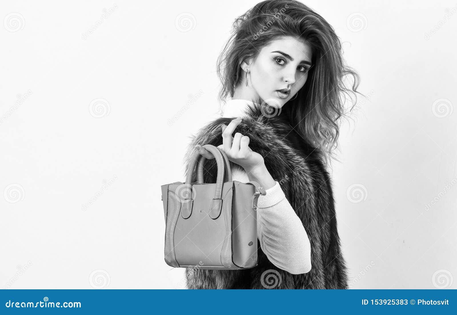 Borsa femminile della tenuta del modello di moda Donna in pelliccia con la borsa su fondo bianco Acconciatura alla moda di signor