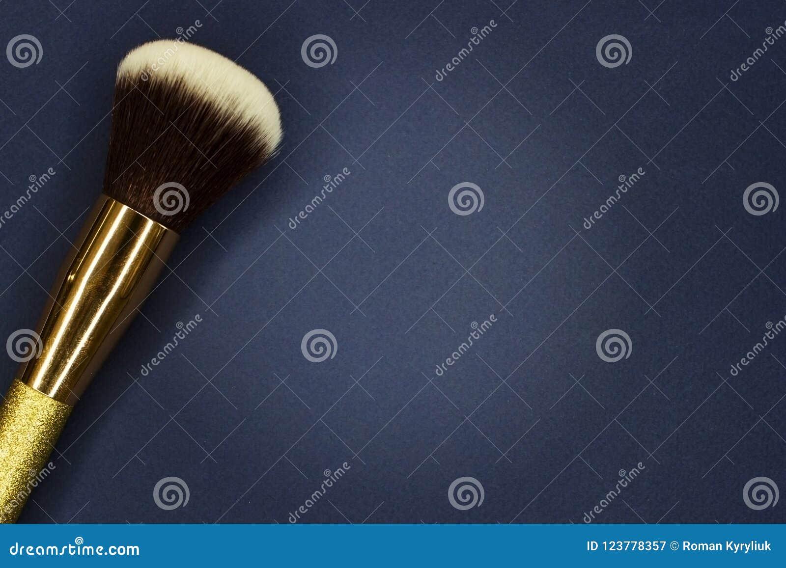 Borste för makeup på ett mörker - blå bakgrund