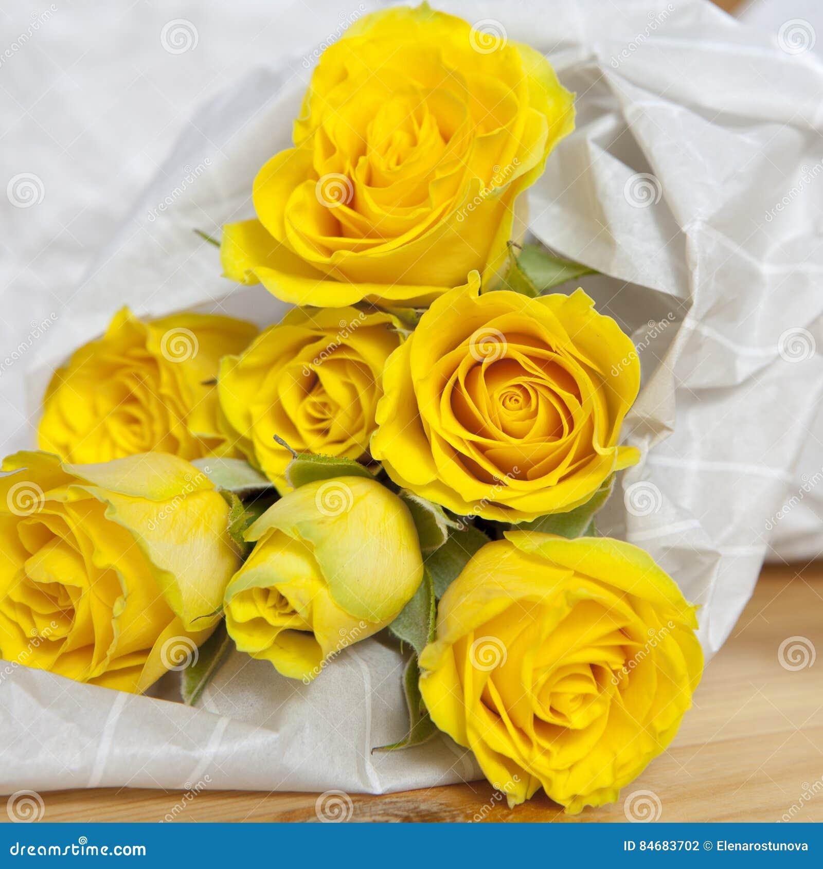Bos van gele rozen in bloemist het verpakken op witte achtergrond