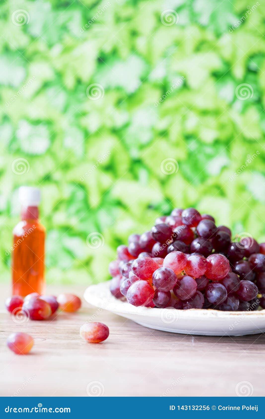 Bos van rode druiven en wijn tegen groene onduidelijk beeldachtergrond
