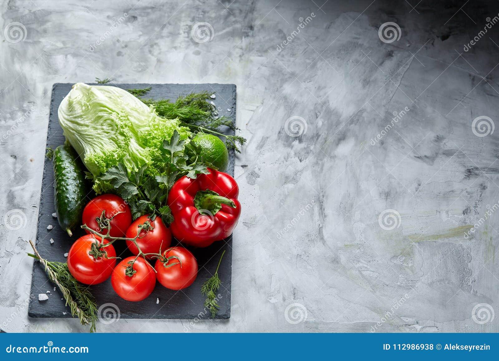 Bos van verse tomaten met groene bladeren op steenachtige raad over witte achtergrond, hoogste mening, close-up, selectieve nadru