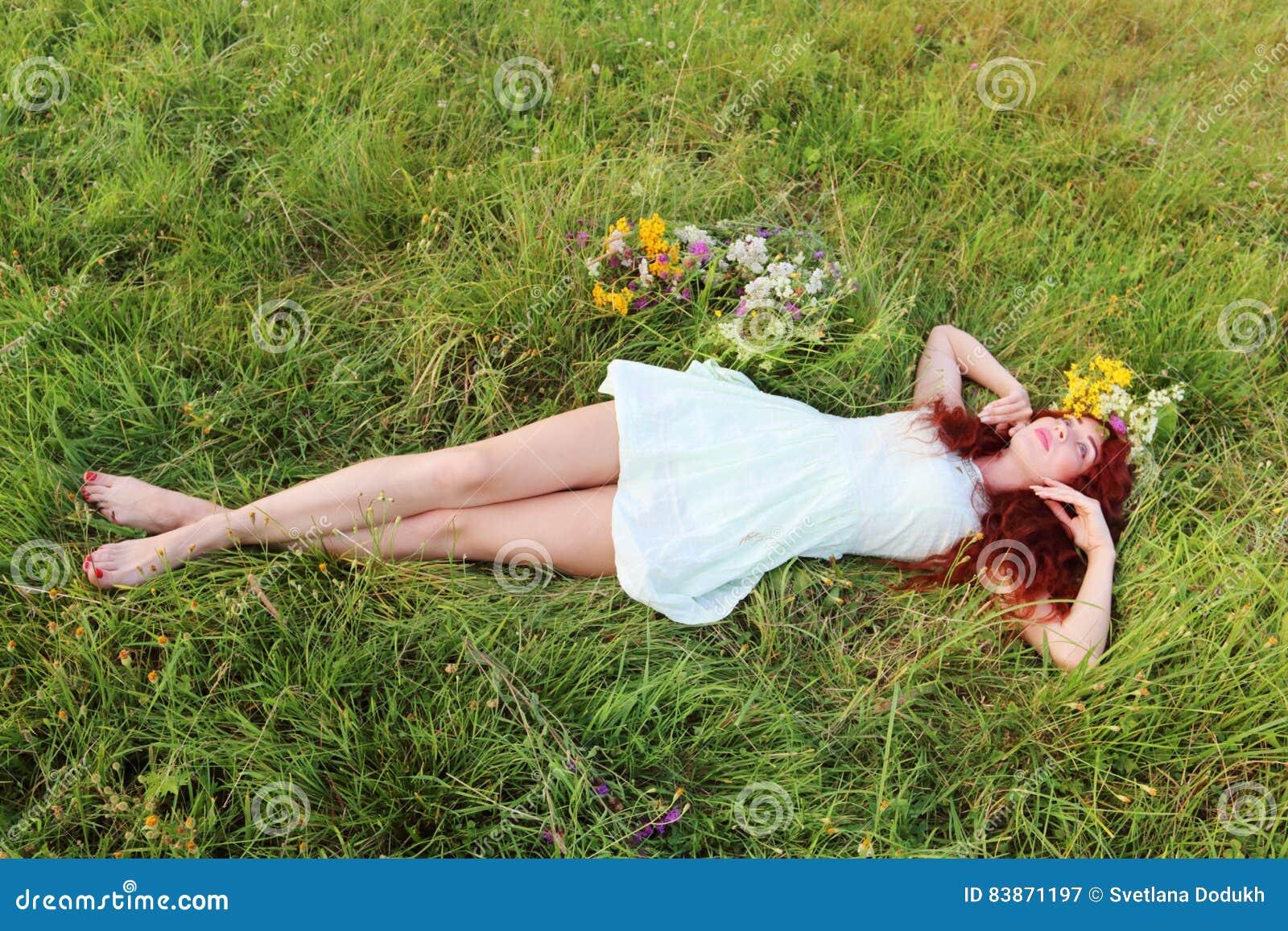 Bosa dziewczyna w wianku kłama na trawie