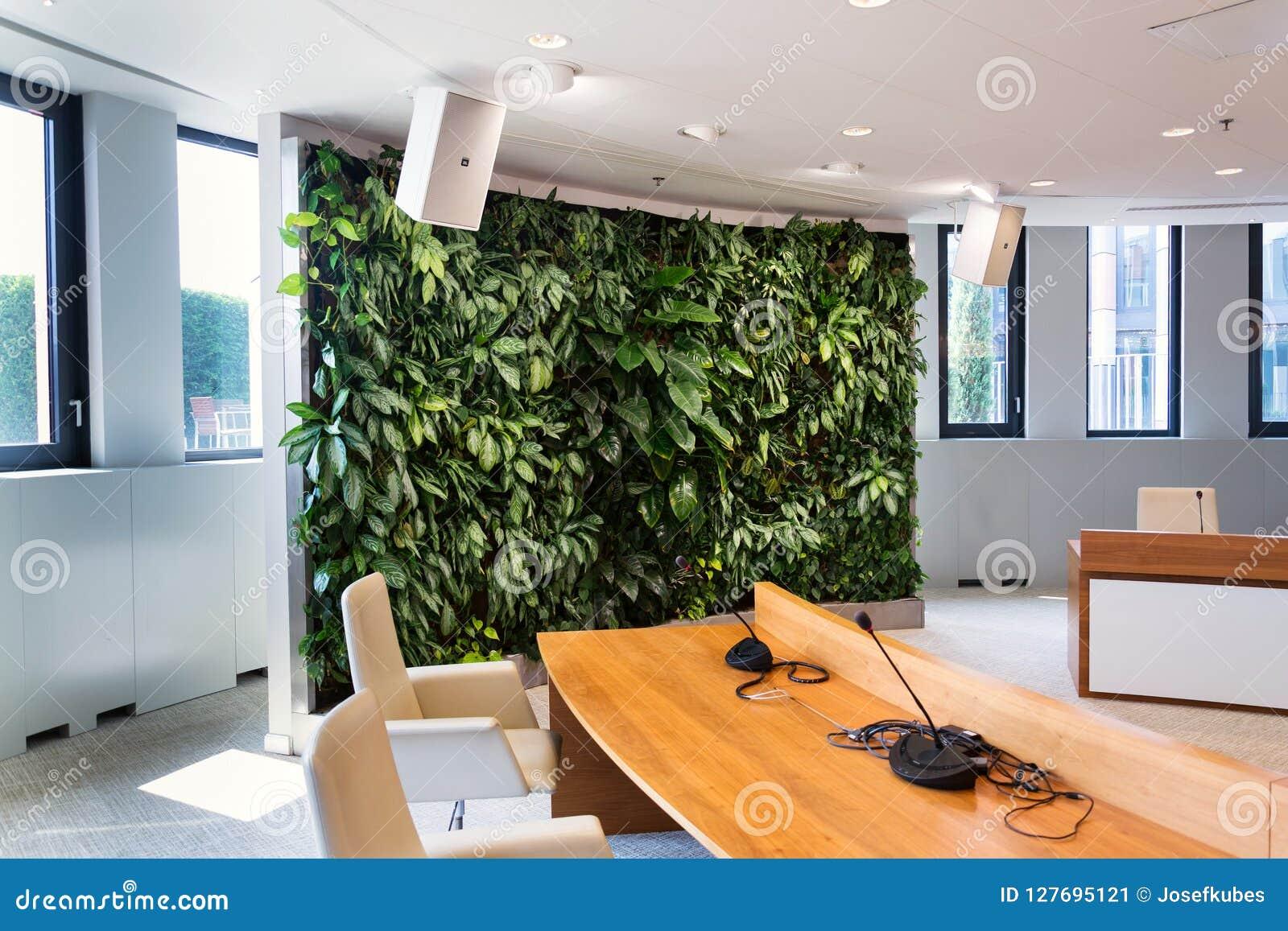 Bosatt grön vägg, lodlinjeträdgård inomhus med blommor och växter under konstgjord belysning i mötestyrelse